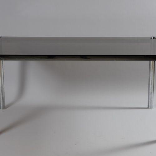 Table rectangulaire à structure en métal chromé, plateau en verre teinté brun.  …