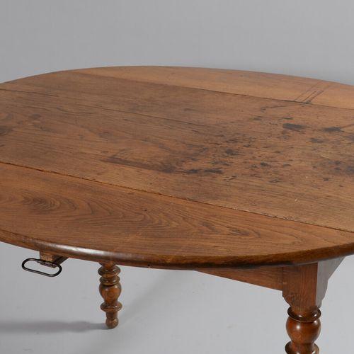 Table à volet en chêne et noyer reposant sur des pieds tournés.  XIXème siècle  …