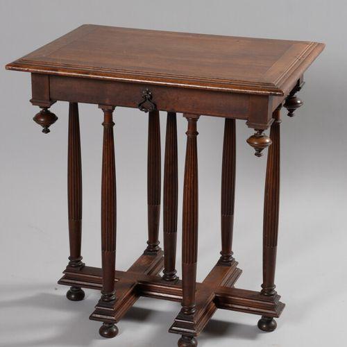Table en noyer reposant sur un piétement à sept colonnes cannelées réunies par u…