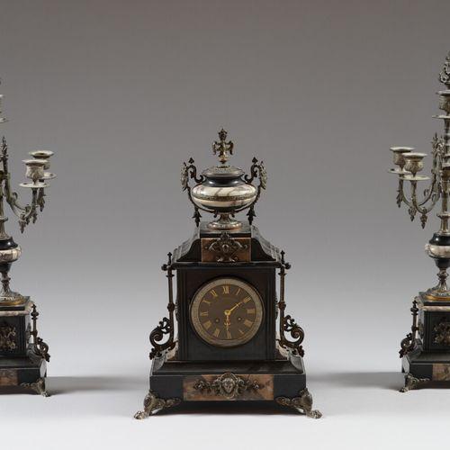 黑色大理石和斑驳的青铜壁炉套装,包括一个时钟和一对有五个灯臂的烛台。  19世纪晚期  高57.5厘米