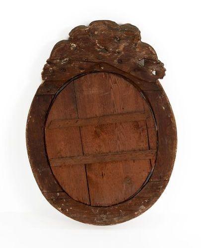 Petit miroir ovale en bois sculpté doré à décor d'un petit bénitier et de deux p…