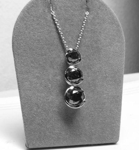 Pendant in white gold on its chain supporting 3 black diamonds in gradation for …