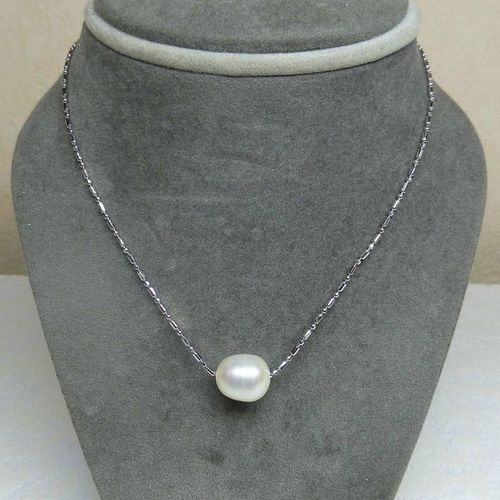 A natural cultured pearl pendant diameter 11 mm approximately on its silver chai…
