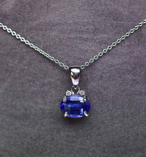White gold pendant centered on a NATURAL oval tanzanite weighing 4.90 c. Enhance…
