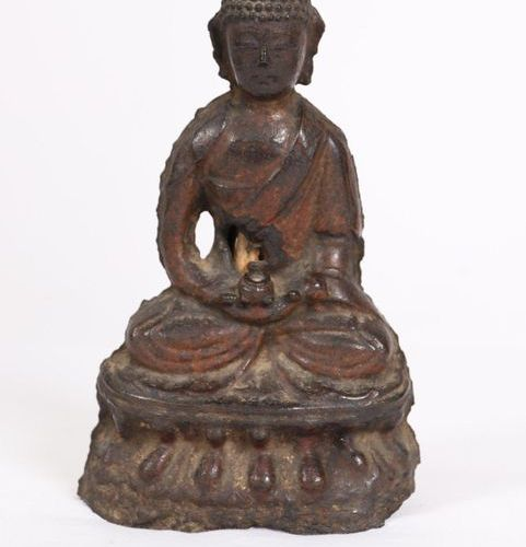 CAST IRON BUDDHA  Shown sitting in a suit, hands folded. It rests on a lotiform …
