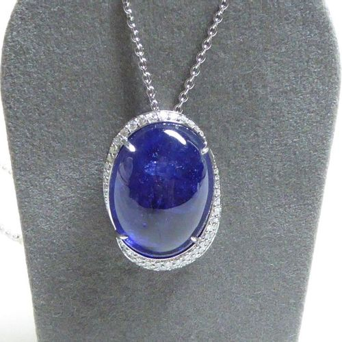 White gold pendant supporting a large oval cabochon tanzanite weighing 26.18 c, …