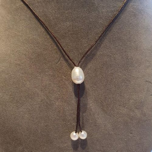 Necklace decorated with 3 natural cultured pearls of baroque shape on a brown an…