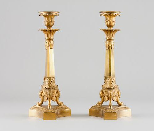A pair of Empire style candle stands Gilt and chiselled bronze  Triangular stand…