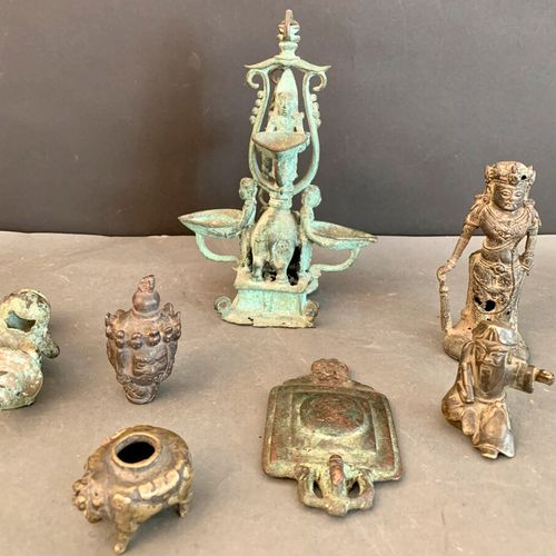 Seven bronzes with an antique or dark green patina including: an oil lamp, a sol…
