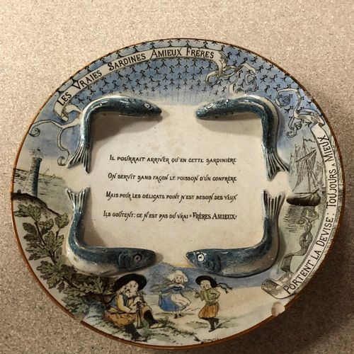 AMIEUX Assiette publicitaire en faïence fine à l'insigne de sardines et décor en…