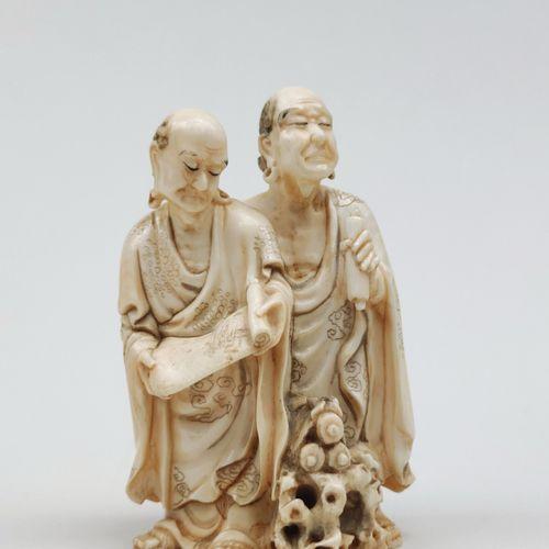 OKIMONO en ivoire représentant deux rakkan occupés avec des rouleaux sacrés, l'u…