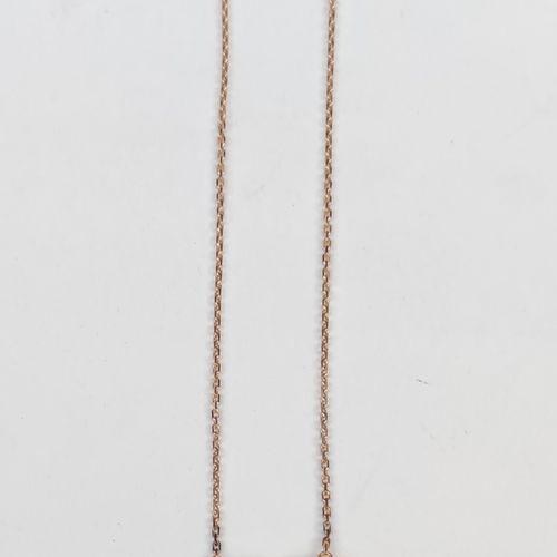 Un collier pendentif en or jaune 750°/00 serti d'une pierre bleu et de diamants …