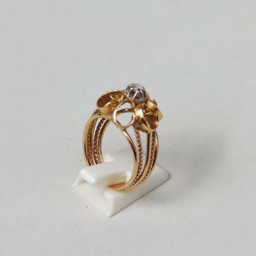 BAGUE en or jaune 750°/°° ajouré à motif de volutes centrées d'un petit diamant …