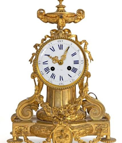 Louis XVI inspired clock in chased and gilded bronze surmounted by a two handled…