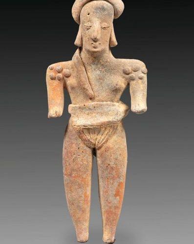 Statuette présentant un personnage féminin debout portant un peigne et un turban…