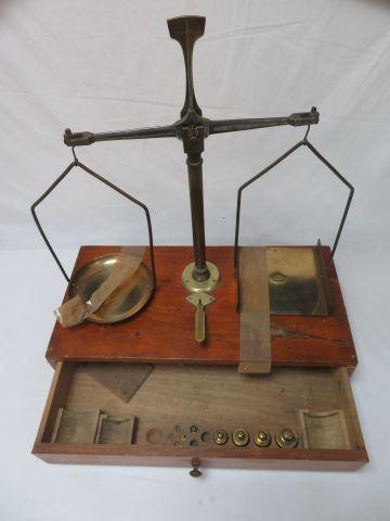 Trébuchet en bois et laiton avec 6 poids dans son tirroir. Hauteur totale 56 cm.…