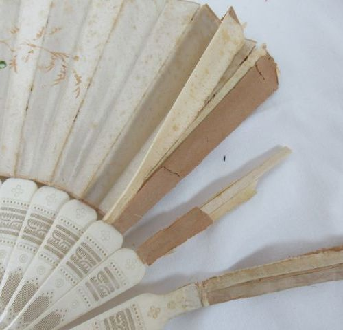 Set of two fans, one in wood with lithographed paper decoration depicting genre …
