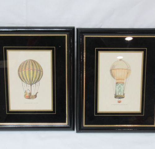 Pair of colour reproductions, featuring hot air balloons. Framed under glass. 29…