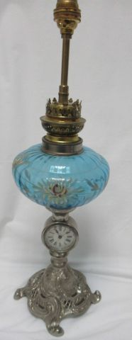 Oil lamp made of enamelled glass and pewter. The base includes a clock/alarm clo…