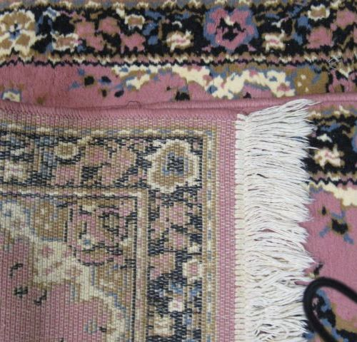 EAST Pair of woollen carpets, with stylized plant decoration on a pink backgroun…
