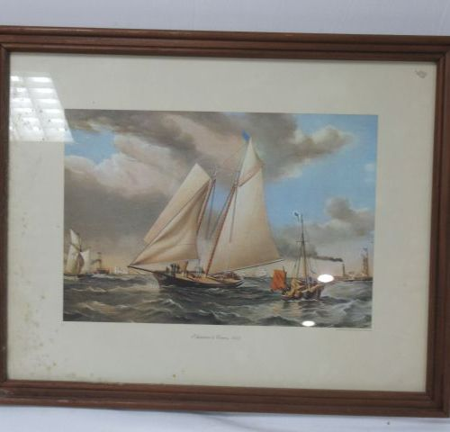 "Natural wood frame containing a colour reproduction (""America in Cowes, ed, NEST…"