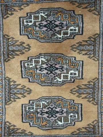 PAKISTAN Wool carpet, geometrically decorated on an ochre background. 74 x 57 cm