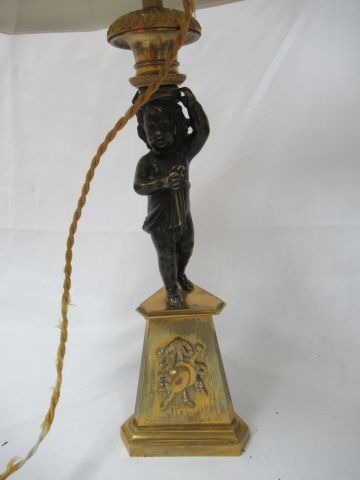 A bronze and brass candlestick, decorated with a putto. Height: 31 cm Mounted as…