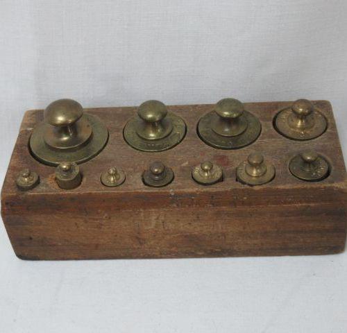 Série de poids en laiton sur leur support en bois. Usures au support. L:13 cm.