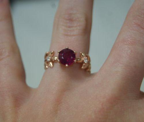 Belle bague en vermeil rose centrée d'un rubis entouré de deux motifs de feuille…