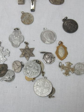LITURGIE Lot comprenant des pendentifs croix et médailles en métal argenté. Quel…