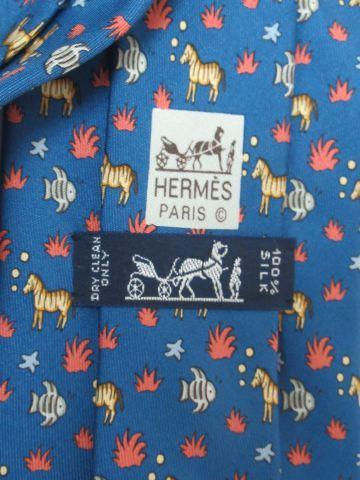 HERMES Cravate en soie, à décor de chevaux. Dans sa pochette