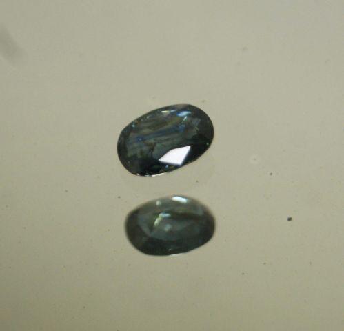 Saphir bleu/vert de taille ovale sur papier.  Inclusions.  Poids : 2,28 cts env.