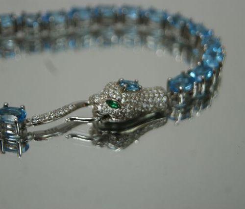 Bracelet en argent, serti de topazes bleues. Fermoir en forme de tête de félin. …