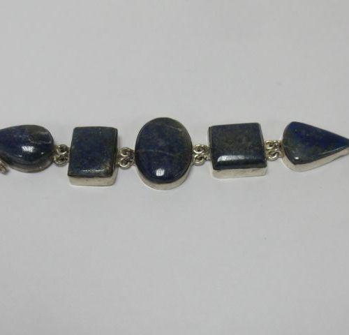 Bracelet en métal argenté, orné de lapis lazuli. Long.: 14 cm (ouvert)