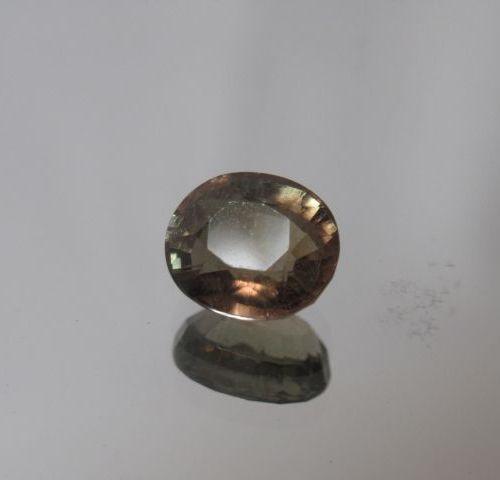 Tourmaline verte avec des reflets bruns de taille ovale sur papier  Poids: 2,25 …