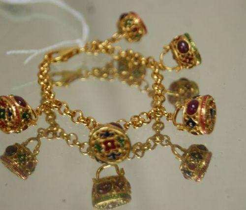 Bracelet en argent vermeillé et émaillé, avec 5 breloques serties de rubis (trai…