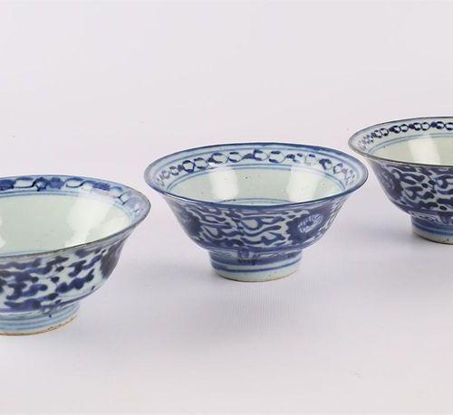 CHINE Trois bols en porcelaine bleu blanc posant sur un talon orné de filet, le …