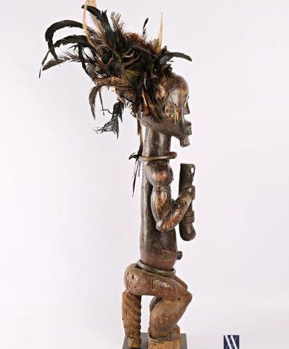 FANG GABON Fétiche d'homme assis tenant un bâton en bois sculpté et patiné, la c…