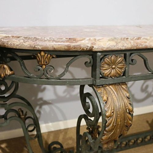 An important wrought iron console, the openwork crosspiece decorated with foliat…