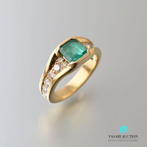750 thousandths yellow gold ring set with a square cut central emerald with seve…