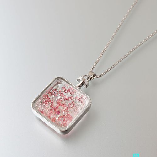 Pendant and its metal chain, the square shaped pendant holding glass beads .  Le…