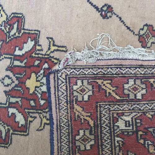 Woollen rug decorated with a central medallion of flowers on a beige background,…