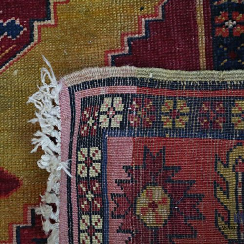 Woollen rug decorated with a central medallion decorated with stylised floral bu…