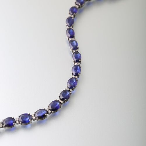 Silver bracelet adorned with oval cut sapphires alternating with small diamonds,…