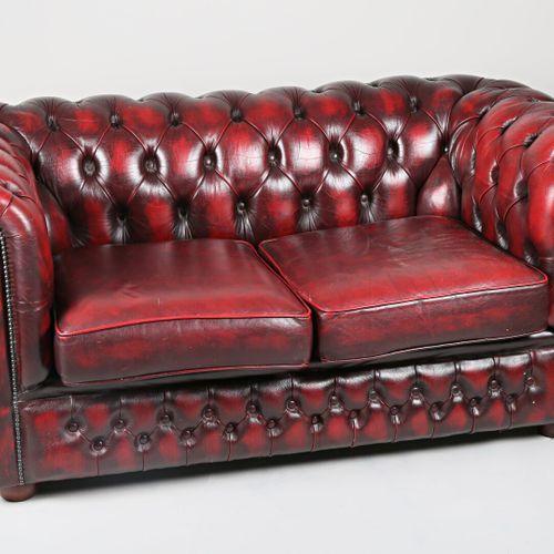 Canapé Chesterfield en simili cuir de couleur cerise, le dossier capitonné, il r…