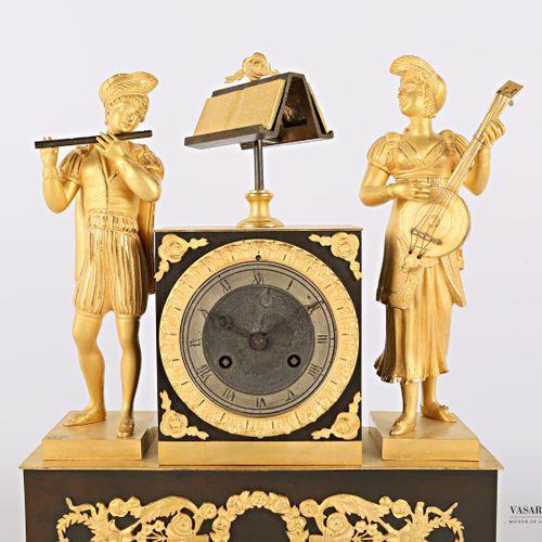 青铜钟有古色古香和镀金,圆形的表盘上有罗马数字的小时和铁路,周边有棕榈花的楣,它被刻在一个终端,装饰有玫瑰花的窗台,后者的两侧有两个游吟诗人,其中一个在吹笛子。…