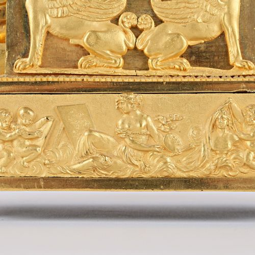 镂空和鎏金的青铜钟,圆形的白色珐琅表盘上标有Terrien in Paris,呈现出罗马数字的小时和阿拉伯数字的分钟,周边的铁轨,镂空的指针,它的顶部是一个坐在…