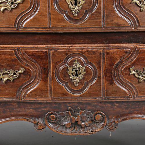 Commode en bois naturel mouluré et sculpté, la façade arbalète ouvre par cinq ti…