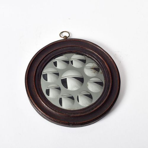 Round witch's mirror composed of a central pellet surrounded by eight smaller pe…