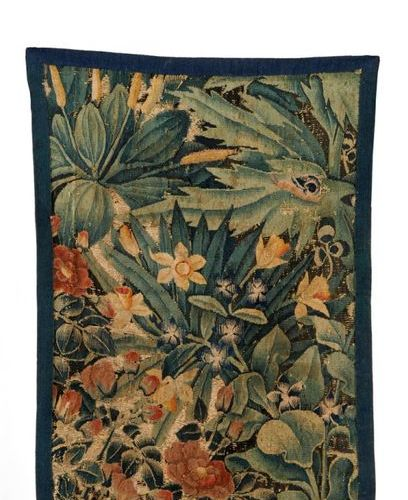 Fragment of a wool and silk tapestry decorated with greenery and flowers. 16th c…